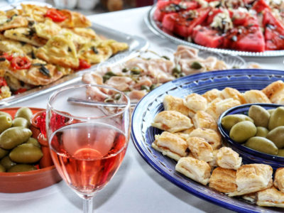 Italian catering buffet with mortadella, olives and rose wine