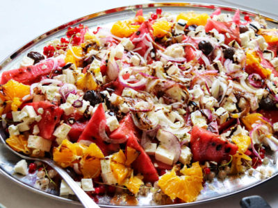 Orange tomato salad with onions and berries