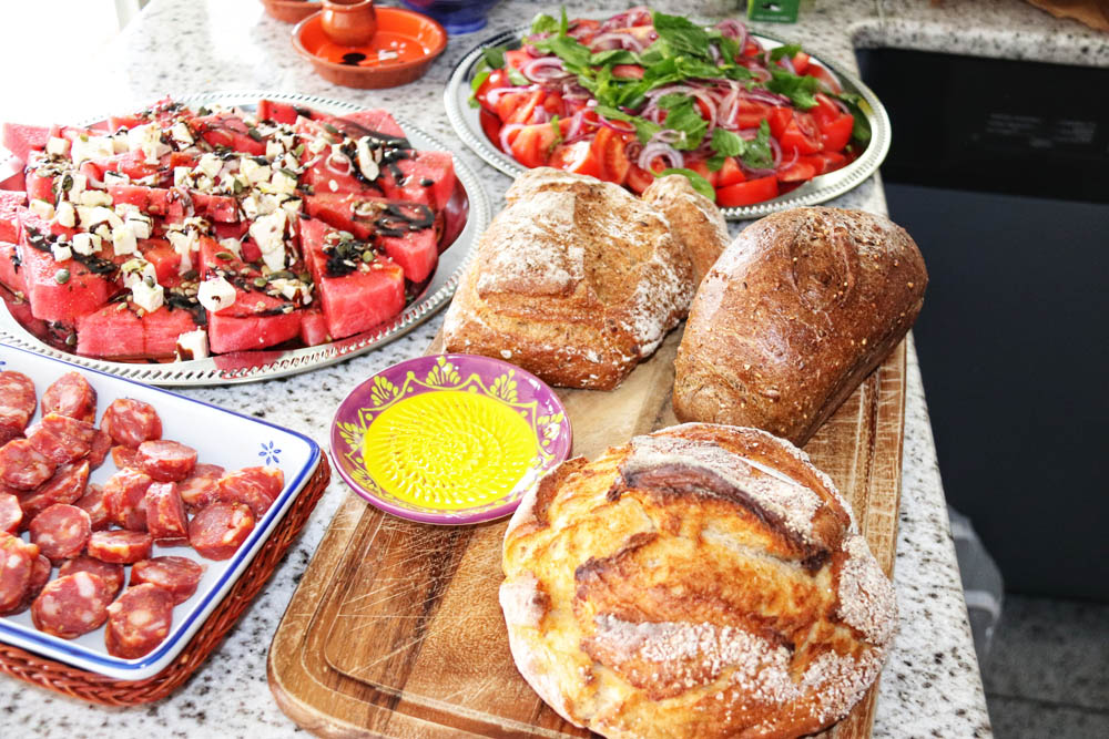 Bread on a wooden cutting board, sausage and water melon salad