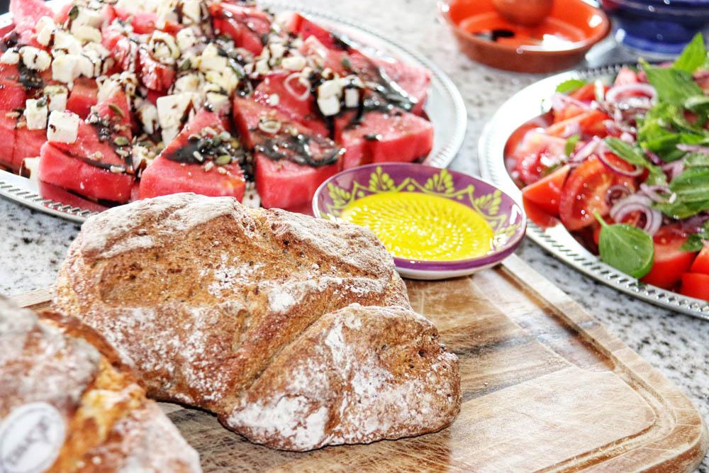 Brot auf einem Holzschneidebrett, Wassermelone Salat auf der Rückseite
