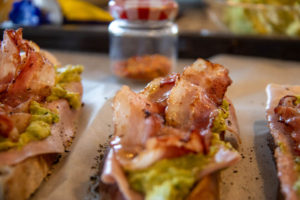 Toasted bread slices on a baking sheet with ham, avocado and bacon on top