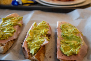 Geröstete Brotscheiben auf einem Backblech mit Schinken und Avocado oben