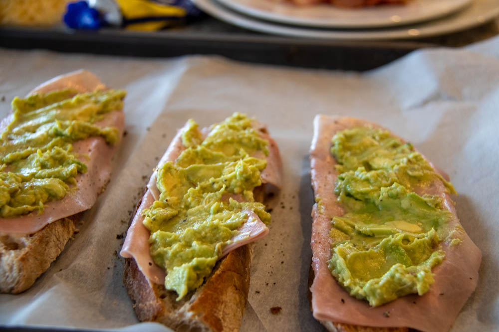Toasted bread slices on a baking sheet with ham and avocado on top