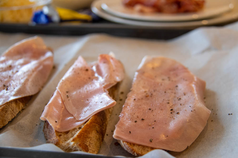 Toasted bread slices on a baking sheet with ham on top