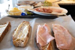 Geröstete Brotscheiben auf einem Backblech mit Béchamel und Schinken oben