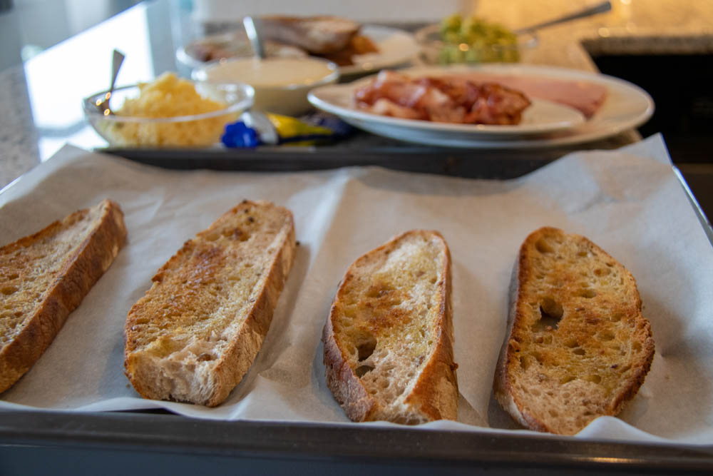 Toasted bread slices on a baking sheet and ingredients for croque madame