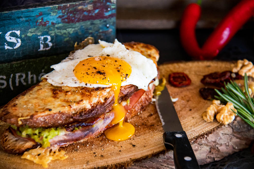 Croque Madame with a fried egg on top, served on a wooden plate