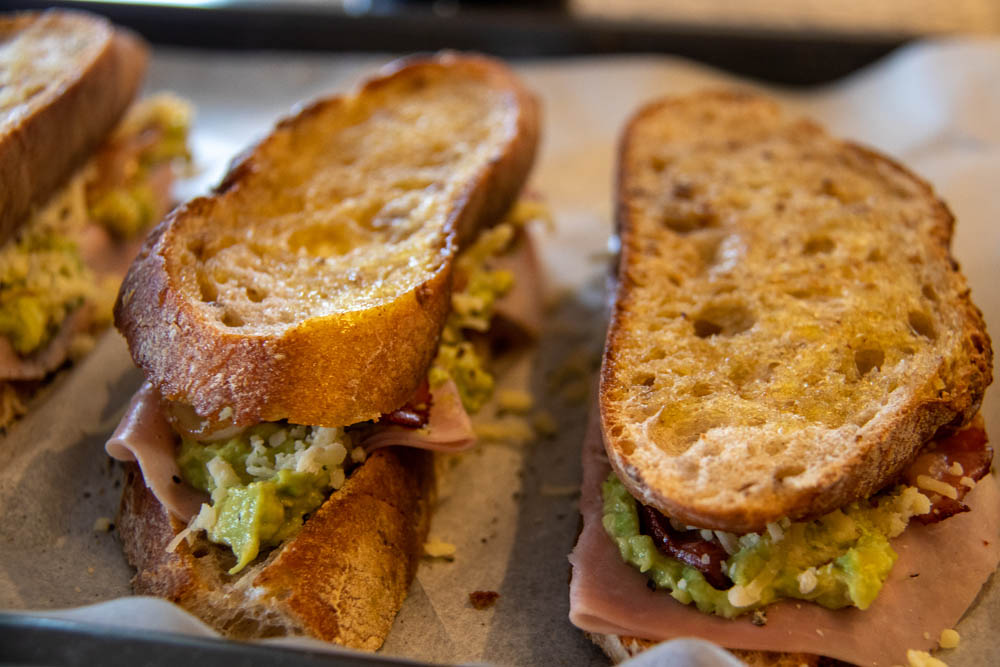 Toasted bread slices on a baking sheet with ham, bacon, avocado and mustard and cheese on top