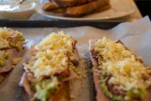 Geröstete Brotscheiben auf einem Backblech mit Schinken, Speck, Avocado und Senf und Käse obendrauf
