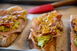 Toasted bread slices on a baking sheet with ham, bacon, avocado and mustard on top