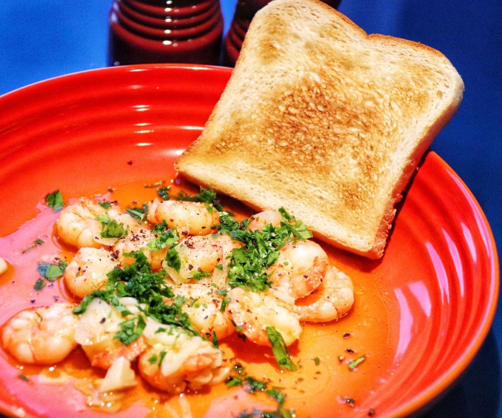 Sauteed garlic shrimps with toast on a orange stoneware pasta bowl