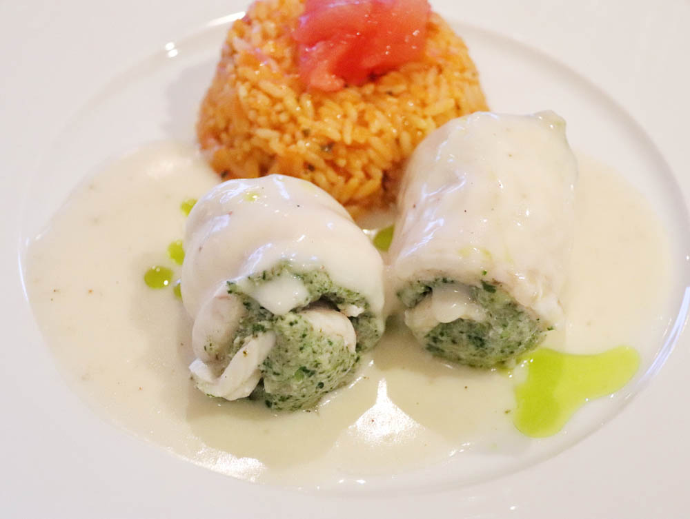 Paupiettes of sole fillet with spinach, hake and mushrooms. Served on a white wine sauce and tomato pilaf rice