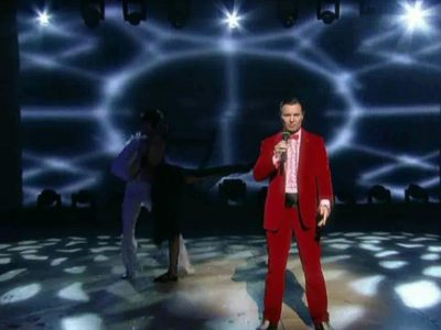 Alessandro Cipriano on stage in Graz, wearing a red suit