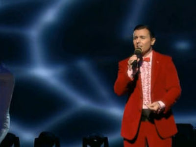 Alessandro Cipriano on stage wearing a red suit